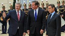 Prime Minister Stephen Harper and his British counterpart, David Cameron, are greeted by French President Nicolas Sarkozy ahead of a summit on Libya's future in Paris on Sept. 1, 2011. (Sean Kilpatrick/THE CANADIAN PRESS)