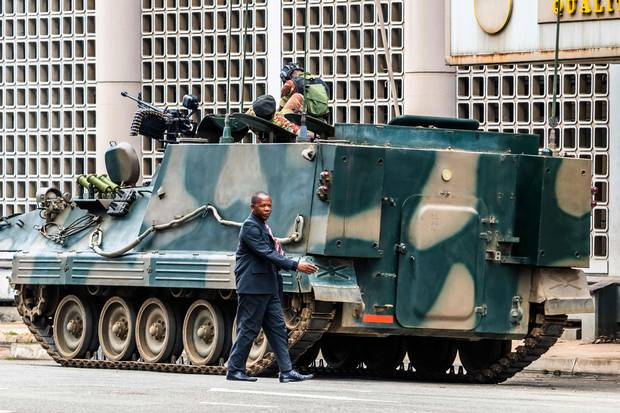 Nov. 16: A man walks past a military tank parked on the side of a Harare street.
