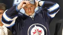 Jacob Trouba pulls on a Winnipeg Jets cap after being chosen ninth overall in the first round of the NHL hockey draft on Friday, June 22, 2012, in Pittsburgh. (Keith Srakocic/AP)