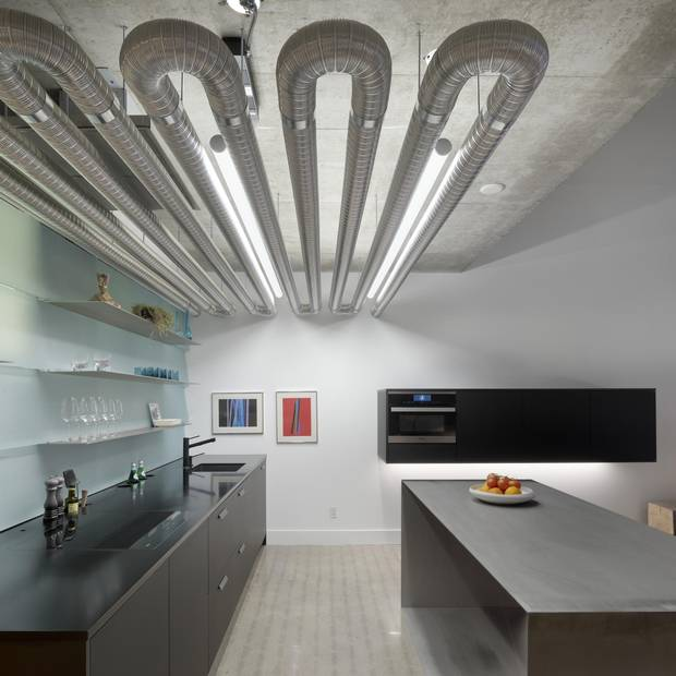 Previously, everything in the kitchen was visually 'messy,' before owner Nima Rafizadeh had some walls blown away and a concrete polishing team brought in. For the staircase, the original wooden treads and risers were refaced with steel while one wall was clad in a custom corrugated aluminum.