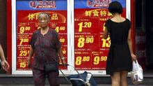 Shoppers walk past and look at a board displaying food prices at a shopping mall in central Beijing, in this August 9, 2011 file picture. China's annual inflation rebounded sharply in March to 3.6 percent, driven by rising food prices, data showed on April 9, 2012. (David Gray/Reuters)