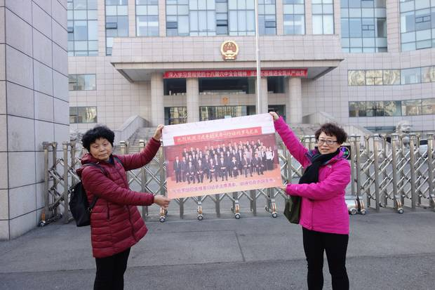 Mr. Wang's wife, Jean Zou, left, and sister Wang Qin hold the photo they say challenges the case against Mr. Wang. One witness testified that he gave Mr. Wang a bribe in person in October, 2009. But he wasn't in China then; he was in Romania, where the photo was taken.