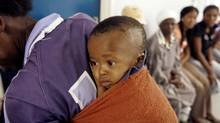 A mother and child await treatment at the Empilisweni Clinic in Worcester, South Africa, on Feb. 4, 2008. (SCHALK VAN ZUYDAM/Associated Press)