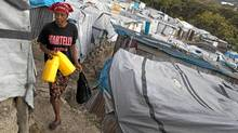 In this Jan. 5 photo, a woman wears a T-shirt with the name of President Michel Martelly as she walks through the Beaubin camp for people displaced by the 2010 earthquake in Petionville, Haiti. (Dieu Nalio Chery/AP/Dieu Nalio Chery/AP)