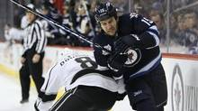 Winnipeg Jets forward Tanner Glass (15) is checked by Los Angeles Kings defenceman Drew Doughty (8) during second period NHL action in Winnipeg on Thursday, December 29, 2011. (JOHN WOODS/THE CANADIAN PRESS)