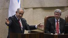 Prime Minister Stephen Harper listens as Israeli Prime Minister Benjamin Netanyahu addresses the Knesset, the Israeli parliament, in Jerusalem on Jan. 20, 2014. (BAZ RATNER/REUTERS)