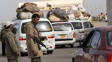 Two Libyan rebels check vehicles crossing toward Egypt at the Egyptian-Libyan border crossing near the border town of Musaed, Libya, on March 16, 2011. (Nasser Nasser/Nasser Nasser/The Associated Press)