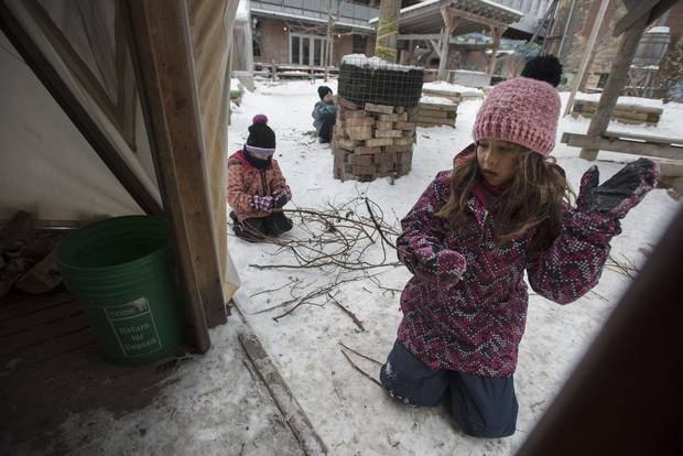 Two young girls sort through twigs looking for the right piece to make hanging ornaments at the Winter Adventure Camp at Evergreen Brick Works on Jan. 3, 2018.