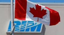 The Canadian flag flies in front of the Research In Motion (RIM) company logo on one of their many buildings, Friday, June 29, 2012 in Waterloo, Ont. (Dave Chidley/THE CANADIAN PRESS)