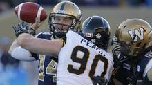 Winnipeg Blue Bombers' Joey Elliott (14) throws despite pressure from Hamilton Tiger-Cats' Greg Peach (90) during the first half of their CFL game in Winnipeg Thursday, August 16, 2012. (The Canadian Press)