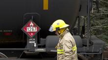 Firefighters in Nantes, Que., inspect a row of none oil tankers sitting on a railway siding there on July 10, 2013. (Peter Power/The Globe and Mail)