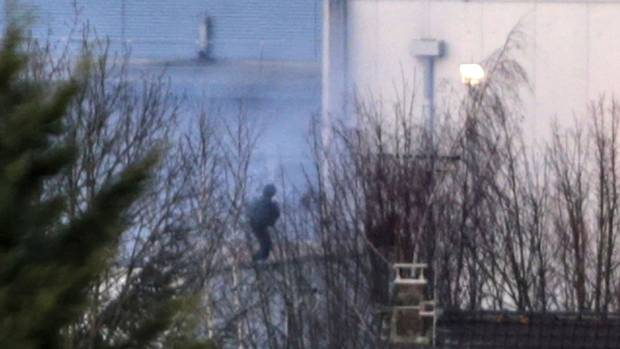 French commandos launch an assault as smoke rises from a building in Dammartin-en-Goele, northeast of Paris, on Jan. 9, 2015.