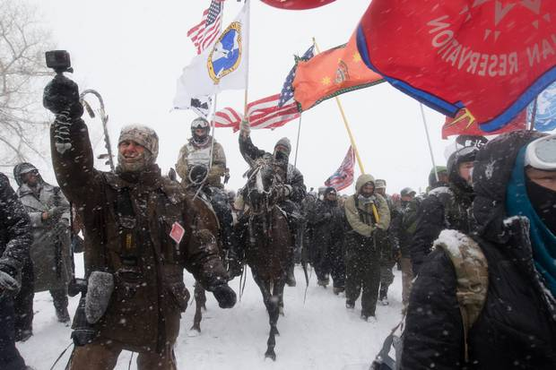 Veterans and supporters march through a blizzard to pray at the Backwater Bridge police barricade. At least a thousand veterans came to stand between police violence.