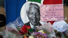 A South African flag with the image of Nelson Mandela on it hangs on a fence along with a note and bouquets of flowers in front of the Town Hall in Cape Town December 6, 2013. South African anti-apartheid hero Mandela died peacefully at home in Johannesburg at the age of 95 on Thursday after months fighting a lung infection, leaving his nation and the world in mourning for a man revered as a moral giant. (STRINGER/REUTERS)
