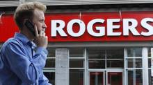 A pedestrian uses his mobile phone while walking past a Rogers store in Ottawa in this file photo. (CHRIS WATTIE/REUTERS)