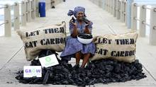 "An activist of British charity Oxfam pretends to eat a piece of coal as a protest aimed at 17th Conference of the Parties (COP17) under the UN Framework Convention on Climate Change (UNFCCC) as she sits between bags reading ""Let Them Eat Carbon"" Dec. 9 in Durban. (Stephane de Sakutin/AFP/Getty Images/Stephane de Sakutin/AFP/Getty Images)"