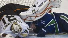 Anaheim Ducks goaltender Curtis McElhinney (L) falls over Vancouver Canucks Mason Raymond during the third period of their NHL hockey game in Vancouver, British Columbia December 8, 2010. REUTERS/Andy Clark (ANDY CLARK)