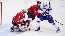 Team Canada goalie Carey Price makes a save as Shea Weber fights off Team Norway's Ken Andre Olimb during the first period of hockey action at the Sochi Winter Olympics February 13, 2014. (John Lehmann/The Globe and Mail)