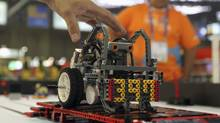 A student touches his mobile robot during the Worldskills Americas 2012 in Sao Paulo November 14, 2012. (Paulo Whitaker/Reuters)