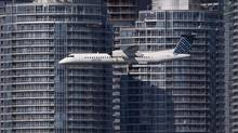A Porter Airlines aircraft passes the Toronto skyline on approach for landing at the Toronto Island Airport Sep 24, 2013. (Moe Doiron/The Globe and Mail)