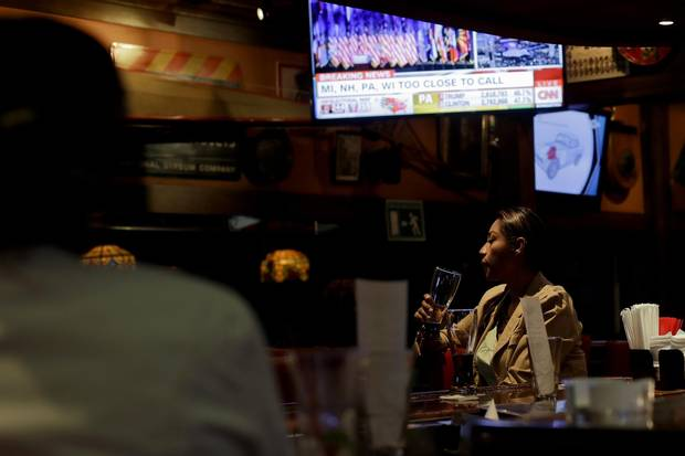 A woman looks on as a screen displays election results at a bar in Tijuana on Nov. 8, 2016.