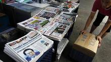 A vendor works beside Hong Kong newspapers showing photos of Zhou Yongkang on Wednesday. China's Communist Party said on Tuesday it had launched a corruption investigation into former domestic security chief Zhou, one of the country's most influential politicians. (BOBBY YIP/REUTERS)