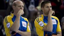 Alberta skip Kevin Martin, left, and third John Morris pause for a moment during the afternoon draw against Northern Ontario at the Tim Hortons Brier in Edmonton, Alta. Monday, March 4, 2013. (The Canadian Press)