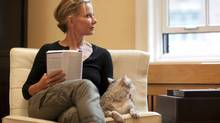 Writer and O Magazine editor Susan Casey reads with her cat, Mouse, in her living room in New York City. (Michael Falco)