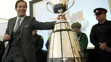 CFL Commissioner Mark Cohon, left, touches the Grey Cup at City Hall during a 100th year celebration that kicked off in Toronto on Friday. (Nathan Denette/THE CANADIAN PRESS)
