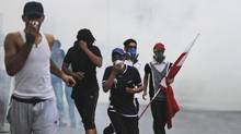 Bahraini anti-government protesters react to tear gas fired by riot police on Thursday, Apr. 12 in Bilad Al Qadeem, Bahrain, on the edge of the capital of Manama. (Hasan Jamali/AP)