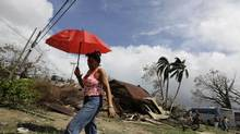 A woman walks past damaged houses after Hurricane Sandy hit Santiago de Cuba Friday. The Cuban government said on Thursday night that 11 people died when the storm barreled across the island. (DESMOND BOYLAN/REUTERS)