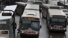 A Toronto Transit Commission workers shuttle passengers to Islington Station after the TTC rail was damaged just outside Kipling Station in the morning in Toronto on Dec. 18, 2013. (Deborah Baic/The Globe and Mail)