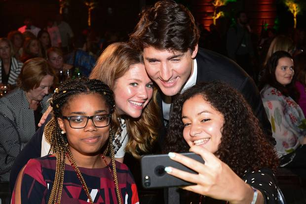 Mr. Trudeau and Ms. Grégoire Trudeau pose for a selfie with young students at the Fortune summit at Washington's Smithsonian American Art Museum.
