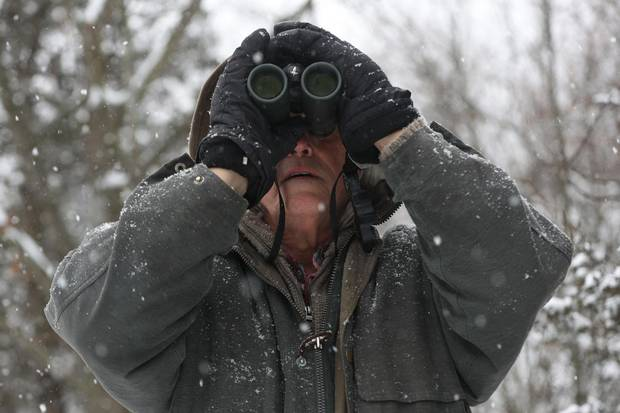 Michael Runtz looks for birds on his trail behind his home in Seeley's Bay, Ont., on Friday Dec. 22, 2017.