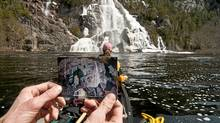 Writer Conor Mihell holds a small print of Algoma Waterfall – a painting of Bridal Veil Falls by J.E.H. MacDonald – in front of the real falls on the Agawa River. (Aaron Peterson/Aaron Peterson/aaronpeterson.net)