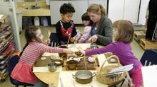 Brandy Cocoroch and her preschool students play with dough at the Queen Street Childcare Centre. (Fernando Morales/The Globe and Mail)