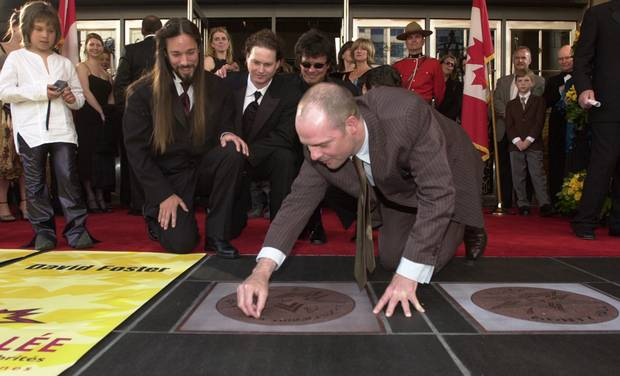 Gord Downie jokingly wipes off lint after the band unveiled their star on the Walk of Fame outside Toronto's Princess of Wales Theatre in May, 2002.