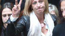 Rachael Szendrei, the mother of Laura Szendrei, gives the victory sign as she and supporters leave court following the verdict at the provincial court in Surrey, B.C., on Oct. 18, 2013. (JONATHAN HAYWARD/THE CANADIAN PRESS)