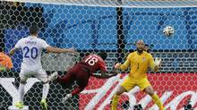 Portugal's Silvestre Varela heads the ball past United States' goalkeeper Tim Howard to score his side's second goal and tie the game 2-2 during the group G World Cup match between the USA and Portugal at the Arena da Amazonia in Manaus, Brazil, Sunday, June 22, 2014. (Martin Mejia/AP)