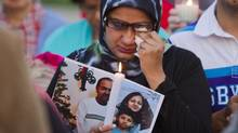 Sadia Nazar weeps at a candlelight vigil as she holds a photo of her co-worker, Jayesh Prajapati. (Tim Fraser for The Globe and Mail)