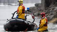 A rescue team searches a river close to a wooded area in Laval, Que., near Montreal, Monday, April 4, 2011, where three-year-old autistic boy Adam Benhamma went missing on March 3. (Graham Hughes/THE CANADIAN PRESS)