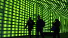 Office workers walk through the green-lit foyer of an office building in Melbourne in this file photo. (MICK TSIKAS/REUTERS)