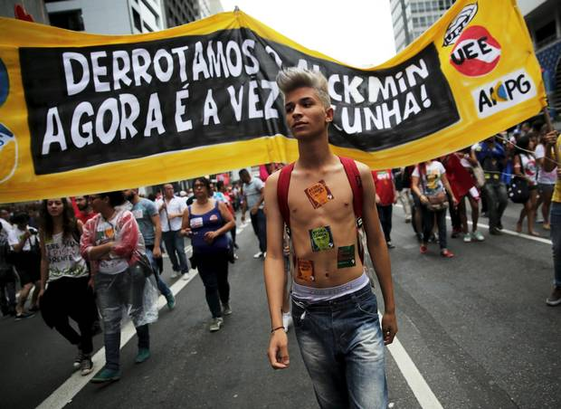 "A demonstrator wears stickers on his body at protests in Sao Paulo on Dec. 16, 2015. The banner reads, ""We have defeated Sao Paulo's State Governor Geraldo Alckmin, now is Cunha."""
