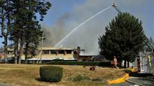 Sooke Fire and Rescue crews work to control a blaze at the Evergreen Centre in Sooke, B.C., on July 31, 2013. (Chad Hipolito for The Globe and Mail)