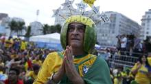 A Brazilian soccer fan wearing a watermelon rind helmet reacts as he watches the match between Brazil and Cameroon, which was broadcast on a large screen at Copacabana beach in Rio de Janeiro, June 23, 2014. (Reuters)