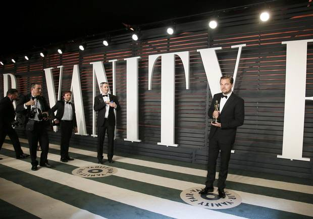 Actor Leonardo DiCaprio holds his award for Best Actor in the The Revenant as he arrives at the Vanity Fair Oscar Party in Beverly Hills, Calif., on Feb. 28, 2016.
