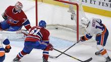 Montreal Canadiens goaltender Carey Price, left, is scored on by New York Islanders' Thomas Hickey, right, as Canadiens' Raphael Diaz defends during overtime NHL action in Montreal, Thursday, February 21, 2013. (Graham Hughes/THE CANADIAN PRESS)