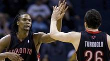 Toronto Raptors forward Chris Bosh (4) high fives teammate forward Hedo Turkoglu of Turkey (26) against the Charlotte Bobcats in the second half during an NBA basketball game in Charlotte, North Carolina March 29, 2010. REUTERS/Chris Keane (CHRIS KEANE)