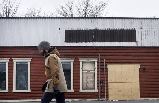 A man walks past a boarded-up business in downtown St. John's.