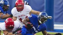 Uof M Carabins ball carrier Rotrand Sene is tackled by McGill Redmens during their opening day game on September 1, 2011. (Christinne Muschi/Christinne Muschi/The Globe and Mail)